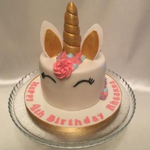 a round white cake with unicorn features (ears, gold horn, pink mane, eyes) and 'happy 4th Birthday' written around the bottom.
