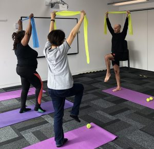 Two older women people doing pilates on a mat with the instructor in front of them